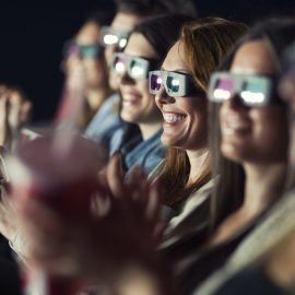 Audience Watching 3-D Movie with 3-d glasses.